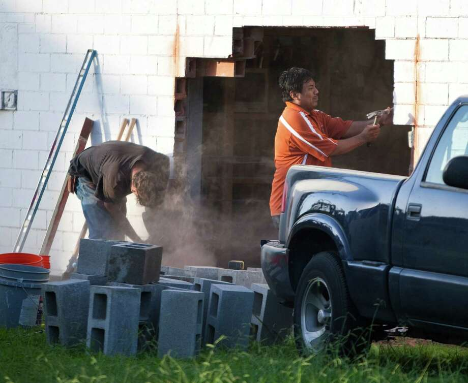 A construction crew repairs a hole where robbers rammed a vehicle into a Cash America. Photo: Nick De La Torre / © 2012  Houston Chronicle