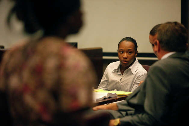Tiffany James, center, watches as her attorneys confer while her sister and witness, Shayla James, left, leaves the courtroom after testifying in Tiffany's murder trial for the death of Antwan Wolford in the Bexar County 399th District Court in San Antonio on Wednesday, July 25, 2012. Photo: Lisa Krantz, San Antonio Express-News / San Antonio Express-News