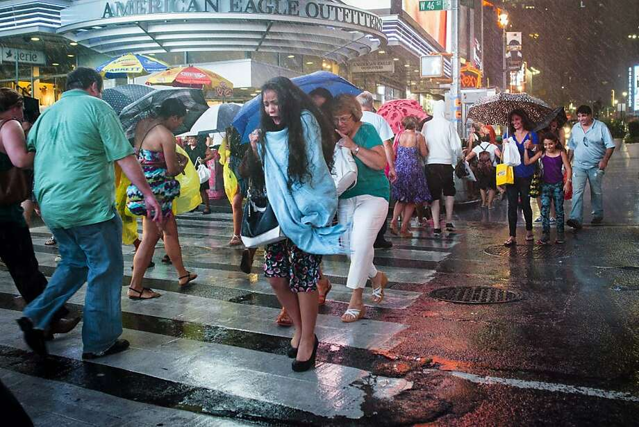 A pedestrian rushes through a torrential downpour in Times Square, Thursday, July 26, 2012, in New York.  (AP Photo/John Minchillo) Photo: John Minchillo, Associated Press