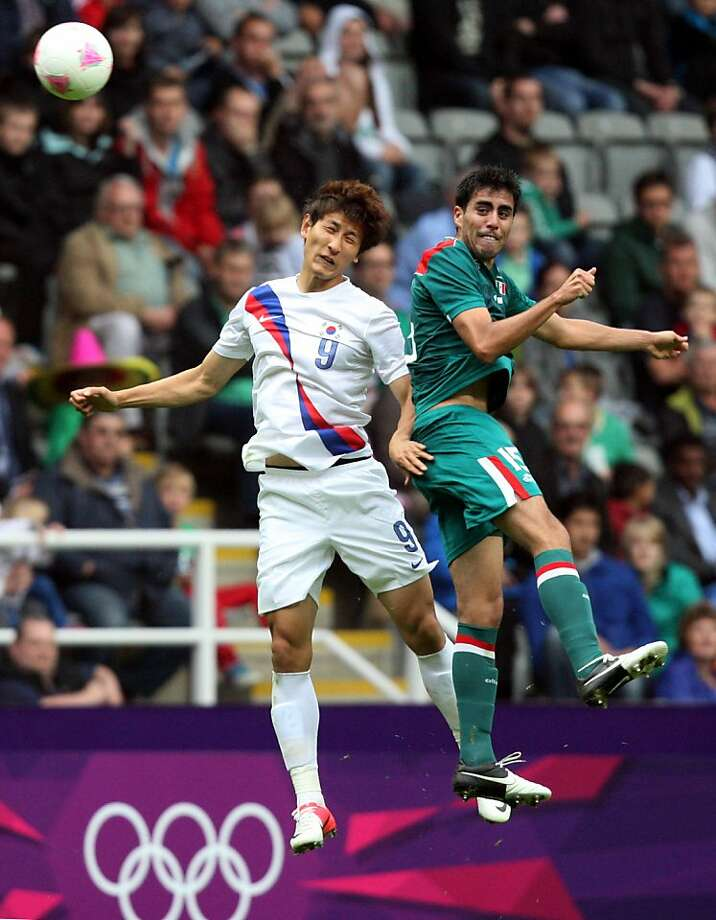 South Korea's Ji Dong-Won, left, vies for the ball with Mexico's Nestor Vidrio, right, during the group B men's soccer match at the London 2012 Summer Olympics, Thursday, July 26, 2012, at St James' Park, in Newcastle, England. (AP Photo/Scott Heppell) Photo: Scott Heppell, Associated Press