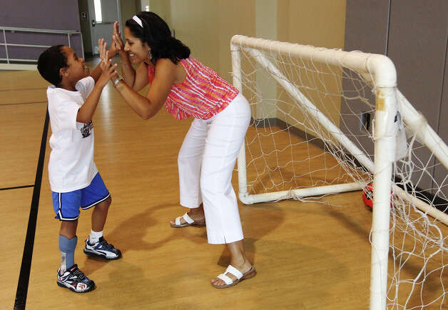 Eight-year-old Micheal (cq) Cole, II, gets high-fived by his mother, Ericka Stevens, after he scores a goal before the start of a soccer clinic on Thursday, July 26, 2012. Morgan's Wonderland hosted the soccer clinic for special needs children with appearances and coaching by San Antonio Scorpions soccer players. Several players were on hand to boost the spirits of the young participants with coaching and encouragement. Representatives from Morgan's Wonderland said they intend on offering more of the soccer clinics in the near future. Photo: Kin Man Hui, San Antonio Express-News / ©2012 San Antonio Express-News