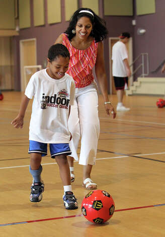 Eight-year-old Micheal (cq) Cole, II, gets ready to kick a soccer ball while chased by his mother, Ericka Stevens before the start of a soccer clinic on Thursday, July 26, 2012. Morgan's Wonderland hosted the soccer clinic for special needs children with appearances and coaching by San Antonio Scorpions soccer players. Several players were on hand to boost the spirits of the young participants with coaching and encouragement. Representatives from Morgan's Wonderland said they intend on offering more of the soccer clinics in the near future. Photo: Kin Man Hui, San Antonio Express-News / ©2012 San Antonio Express-News