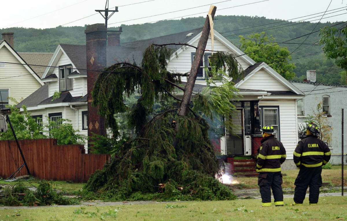 Elmira N.Y., firefighters watch an electric wire fire closely after a possible tornado struck the area, Thursday, July 26, 2012, in Elmira N.Y. Power lines and trees were toppled and hospitals were placed on disaster alert but there were no immediate reports of injuries after a possible tornado hit the city of Elmira Thursday afternoon, Chemung County Office of Fire and Emergency Management spokeswoman Karen Miner said.