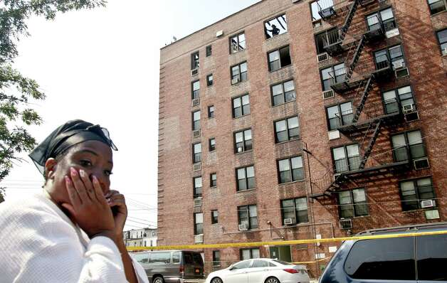 Valma Brown reacts while on a phonecall outside her apartment building which was earlier engulfed fire on its upper floors in the Brooklyn borough of New York, Thursday, July 26, 2012.  Brown was alerted by a neighbor as she slept and ran outside in a robe and with her pets. The blaze injured dozens of firefighters and forced the evacuation of more than 100 families to a temporary Red Cross shelter. Photo: Bebeto Matthews, AP / AP