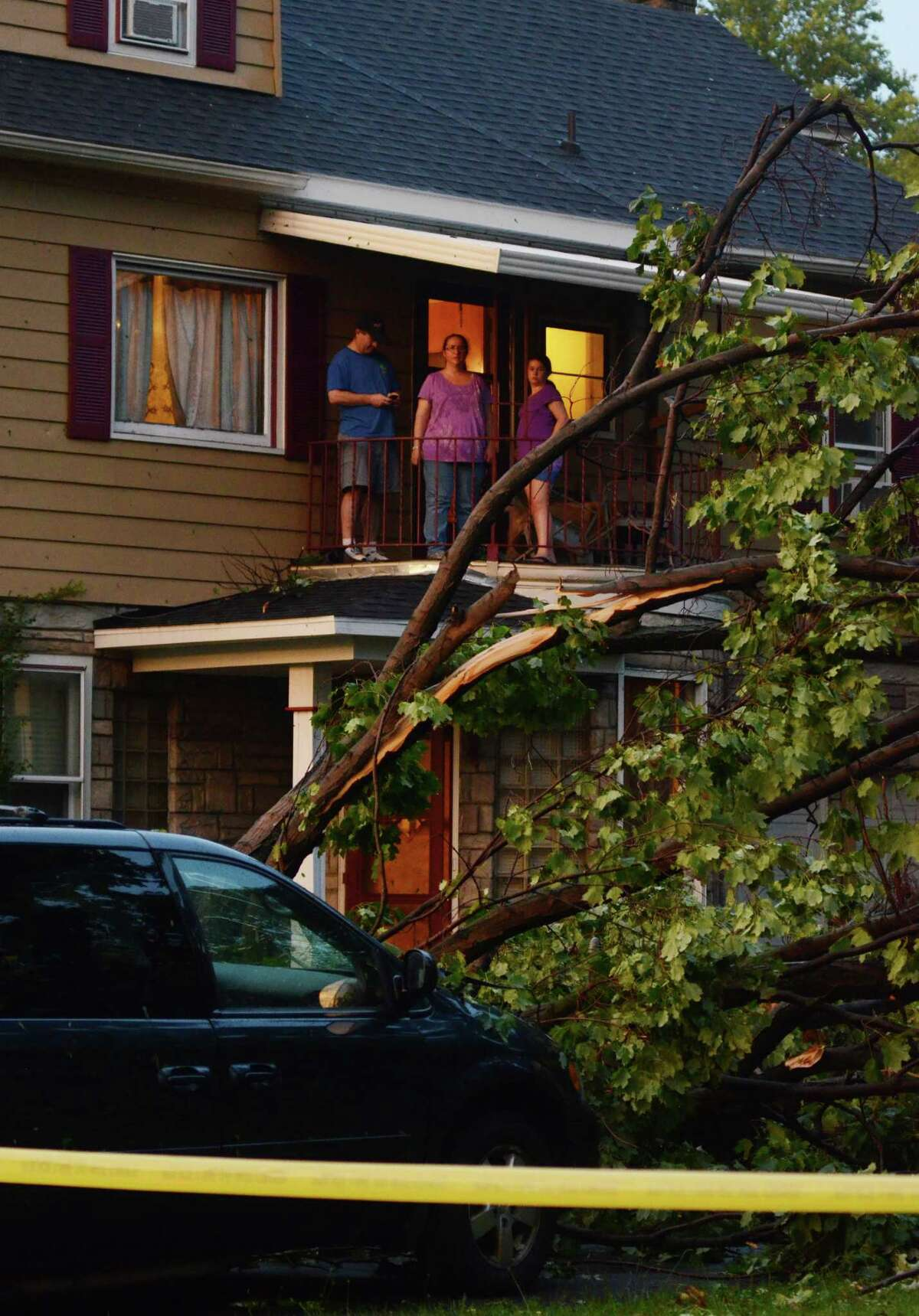 A family surveys the damage surrounding their property in Elmira N.Y., after a possible tornado struck the area, Thursday, July 26, 2012. The storm brought down trees and power lines, tore roofs off some buildings and caused motor vehicle accidents. Utilities report more than 20,000 customers without power in the area.