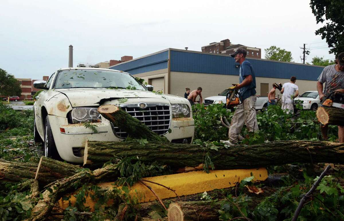 People work en masse to break-up felled trees and free cars underneath them in Elmira N.Y., after a severe storm in the area, Thursday, July 26, 2012. Power lines and trees were toppled and hospitals were placed on disaster alert but there were no immediate reports of injuries after a possible tornado hit the city of Elmira Thursday afternoon, Chemung County Office of Fire and Emergency Management spokeswoman Karen Miner said.