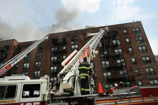 NEW YORK, NY - JULY 26: Firefighters battle a six-alarm fire at a seven-story apartment building in the Prospect Lefferts Gardens of Brooklyn on July 26, 2012 in New York City. Fire officials have reported 14 injuries among residents and firefighters at the building, which houses 115 residential units. Photo: Spencer Platt, Getty Images / 2012 Getty Images