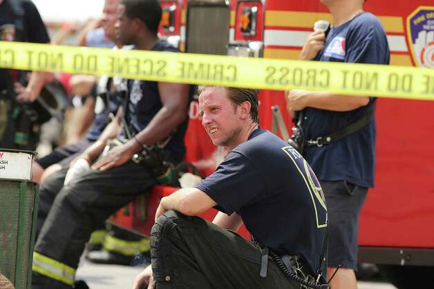 NEW YORK, NY - JULY 26: New York City firefighters rest at the scene of a six-alarm fire at a seven-story apartment building in the Prospect Lefferts Gardens of Brooklyn on July 26, 2012 in New York City. Fire officials have reported 14 injuries among residents and firefighters at the building, which houses 115 residential units. Photo: Spencer Platt, Getty Images / 2012 Getty Images