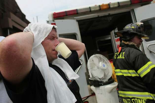 NEW YORK, NY - JULY 26: A New York City firefighter cool off at the scene of a six-alarm fire at a seven-story apartment building in the Prospect Lefferts Gardens of Brooklyn on July 26, 2012 in New York City. Fire officials have reported 14 injuries among residents and firefighters at the building, which houses 115 residential units. Photo: Spencer Platt, Getty Images / 2012 Getty Images