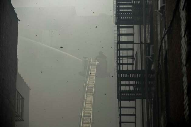 Members of the New York Fire Department fight a blaze at an apartment building in the Brooklyn borough of New York, July 26, 2012. Officials believe the six-alarm fire was sparked by lightning. (Robert Stolarik/The New York Times) Photo: ROBERT STOLARIK, NYT / NYTNS