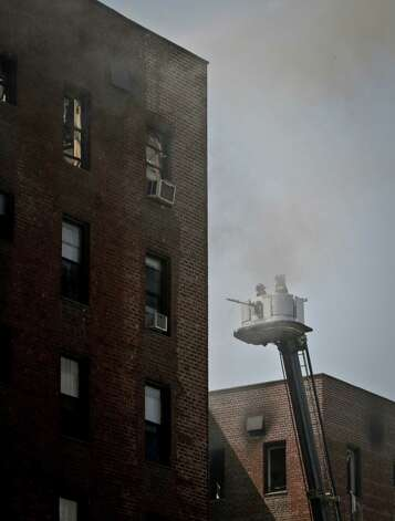 Firefighters are lifted in a ladder bucket to a smoldering area of an apartment building that was earlier engulfed in fire in the Brooklyn borough of New York Thursday, July 26, 2012.  The blaze injured dozens of firefighters and forced the evacuation of more than 100 families to a temporary Red Cross shelter. Photo: Bebeto Matthews, AP / AP
