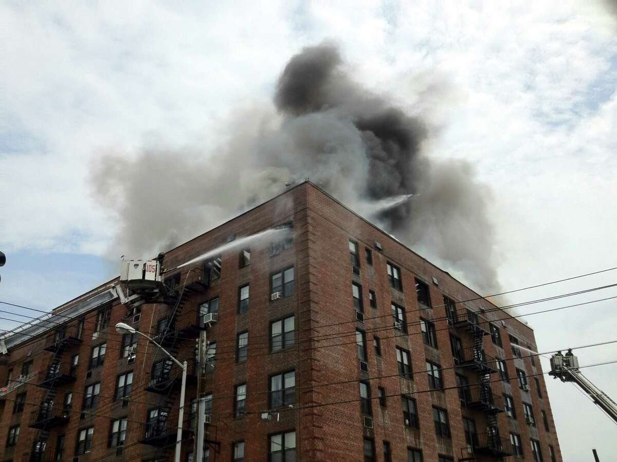 Firefighters use aerial equipment to battle a roaring fire on the upper floors of an apartment building in the Brooklyn borough of New York, Thursday, July 26, 2012. Twenty-six firefighters were hurt fighting the blaze and 100 families were forced to leave the building. (AP Photo/WABC-TV) MANDATORY CREDIT