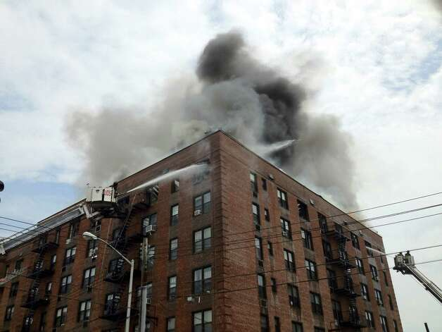 Firefighters use aerial equipment to battle a roaring fire on the upper floors of an apartment building in the Brooklyn borough of New York, Thursday, July 26, 2012. Twenty-six firefighters were hurt fighting the blaze and 100 families were forced to leave the building. (AP Photo/WABC-TV) MANDATORY CREDIT Photo: AP / WABC-TV