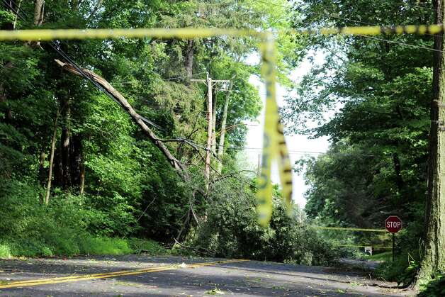A tree limb knocked down in a late day storm on Thursday July 26, 2012, sits on the power lines on Morehouse Highway in Fairfield, Conn. on Friday July 27, 2012. Photo: Cathy Zuraw / Connecticut Post