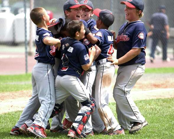 Danbury players celebrate winning the Cal Ripken 10-year-old New England regional tournament championship Friday at Rogers Park. Danbury beat Arlington, Mass., 11-5, in the title game. Photo: Barry Horn / The News-Times Freelance