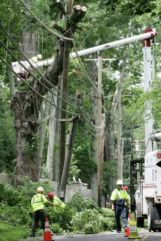 Workers from Lewis Tree Service continued to remove a tree on North Street Friday, July 27, 2012, which came down on power lines during Thursday night's storm.  The street remained closed Friday afternoon. Photo: David Ames / Greenwich Time