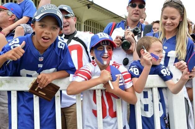 Giants fans Jacob Franco, 10, left, of Richmond, Via.; Baltazar Diaz, 9, of East Greenbush; and his brother Nicolas Diaz, 7, at right, cheer their favorite players at NY Giants training camp at UAlbany Friday July 27, 2012. (John Carl D'Annibale/Times Union) Photo: John Carl D'Annibale
