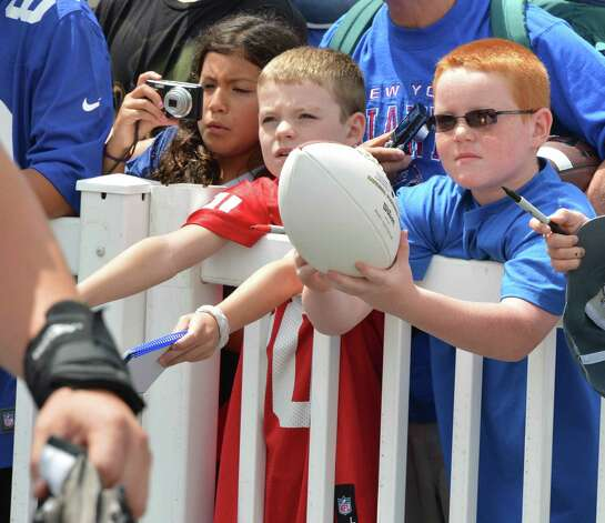 Giants fans Samantha Gomez, 9, left, of Slingerlands; Liam Farrell, 8, of Watertown, Conn.; and Richie Tamsett, 7, of Canajoharie, at right, try to get players' attention during NY Giants training camp at UAlbany Friday July 27, 2012.  (John Carl D'Annibale/Times Union) Photo: John Carl D'Annibale