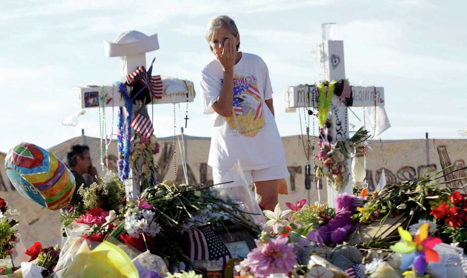 Barb Lee, of Aurora, Colo., cries as she views crosses at the memorial to victims of the movie theater shooting. Readers exchange ideas on gun control. Photo: Ted S. Warren, AP / AP