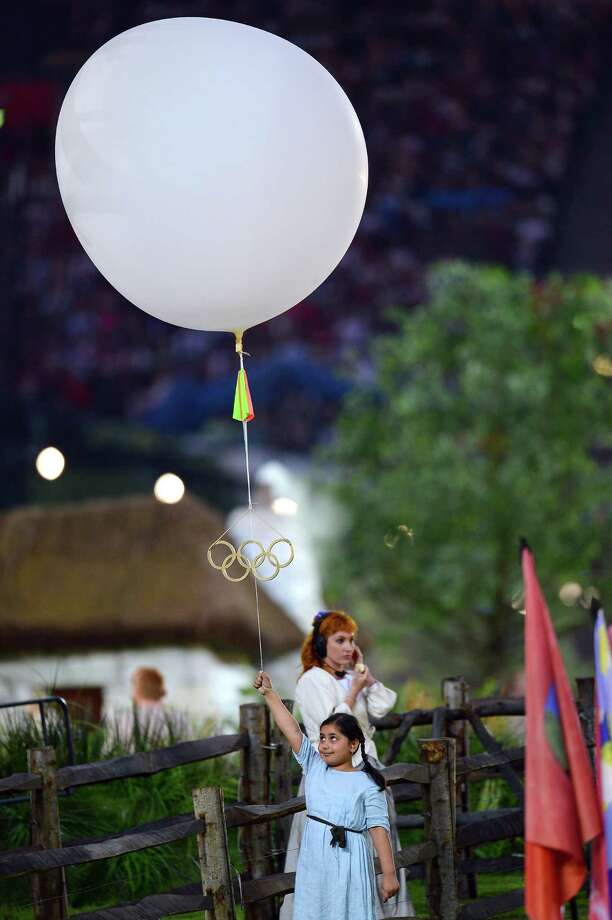 A young performer holds a balloon bearing the Olympic rings during the Opening Ceremony of the London 2012 Olympic Games at the Olympic Stadium on July 27, 2012 in London, England. Photo: Lars Baron, Getty Images / 2012 Getty Images