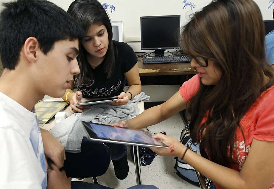 Rosalinda Barron, behind, 16, learns how to work her iPad 2 with Alexis Cantu, right, 15, and Brian Hernandez, 14, in their geometry class Monday Feb. 27, 2012 at McAllen Memorial High School in McAllen, Texas. McAllen Independent School District began handing out iPads and iPod Touch devices Monday morning and plan on providing the electronic devices to about 25,000 district wide students over the next 12 months. (AP Photo/The Monitor, Nathan Lambrecht) Photo: Nathan Lambrecht, Associated Press