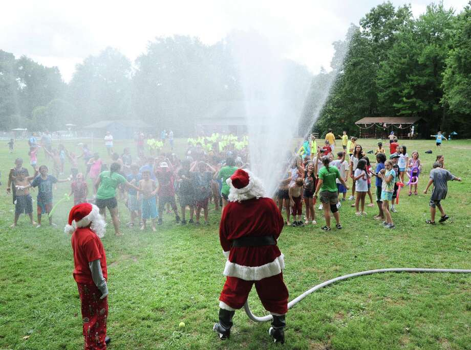 "Santa sprays water from a fire hose onto campers during his annual ""Christmas in July"" visit to the Boys & Girls Club of Greenwich Camp Simmons Friday afternoon, July 27, 2012. Photo: Bob Luckey / Greenwich Time"