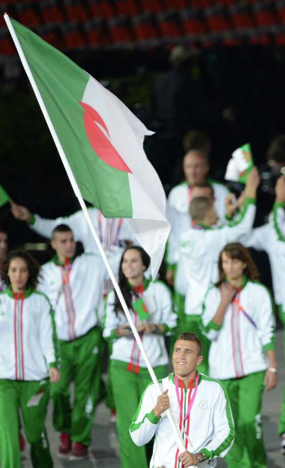 Algeria's flagbearer Abdelhafid Benchabla leads his delegation during the opening ceremony of the London 2012 Olympic Games in the Olympic Stadium in London on July 27, 2012.  AFP PHOTO / CHRISTOPHE SIMON        (Photo credit should read CHRISTOPHE SIMON/AFP/GettyImages) Photo: CHRISTOPHE SIMON, AFP/Getty Images / 2012 AFP