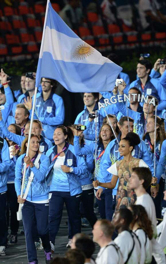 Argentina's flagbearer Luciana Aymar carries the flag as she leads her delegation during the opening ceremony of the London 2012 Olympic Games in the Olympic Stadium in London on July 27, 2012.  AFP PHOTO / CHRISTOPHE SIMON        (Photo credit should read CHRISTOPHE SIMON/AFP/GettyImages) Photo: CHRISTOPHE SIMON, AFP/Getty Images / 2012 AFP