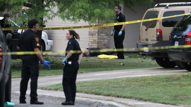 San Antonio police and investigators work at the scene of a fatal shooting July 27 in the 2000 block of Field Wood on the West Side. Officer Michael Garza, who shot and killed the ex-boyfriend of his former roommate, was put on indefinite suspension Tuesday. Photo: JOHN DAVENPORT, San Antonio Express-News / SAN ANTONIO EXPRESS-NEWS