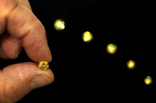 Funeral director Don van Straaten (cq) shows diamonds made from cremated remains at Alta Mesa Funeral Home in Palo Alto, Calif., Thursday, July 26, 2012.  A company, LifeGem, takes the carbon from cremated remains and grows a diamond crystal with it.  They can be made into yellow diamonds, like the ones shown, or colorless, blue, red, or green. Photo: Sarah Rice, Special To The Chronicle