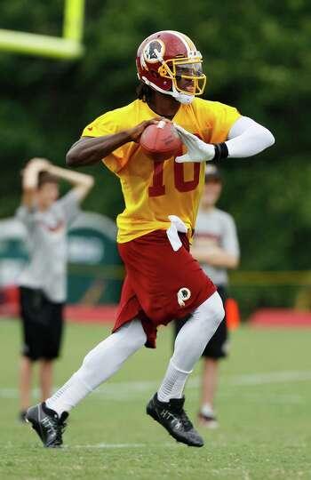 Washington Redskins quarterback Robert Griffin III (10) throws on the run during NFL football traini