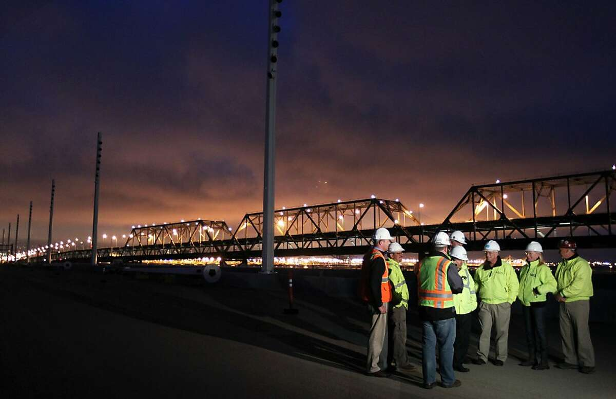 Caltrans engineers and architects along with sub contractors wait for the new Bay Bridge lights to be turned on next to the old boxed steal structure that will be replaced in fall of 2013. New state of the art lights were tested on the Self-Anchored Suspension Span of the new Bay Bridge Thursday July 26, 2012. The light source comes from 273 light polls with a total of 1,521 fixtures that each house 25 to 50 LED?•s lights that are expected to last 10-15 years before they are replaced, and will only use about half the energy. The new span is expected to open in fall of next year 2013.