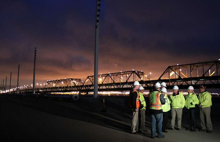 Caltrans engineers and architects along with sub contractors wait for the new Bay Bridge lights to be turned on next to the old boxed steal structure that will be replaced in fall of 2013.  Photo: Lance Iversen, The Chronicle