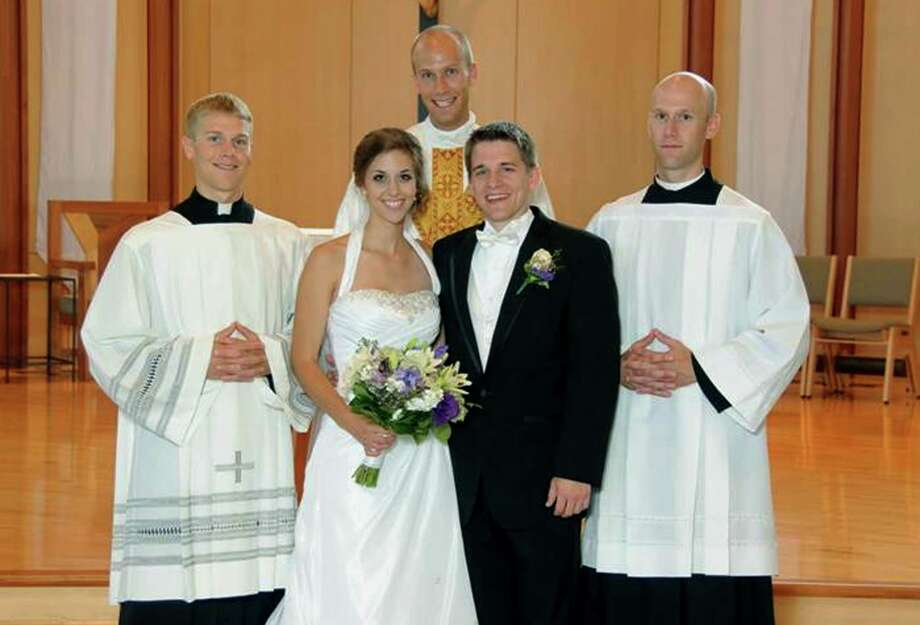 A July 23, 2011, photo provided by Bernadette Strand shows Father Luke Strand, center, after marrying sister Theresa and Christopher Krausert in Dousman, Wis. Also shown is Jacob Strand, left, and Vincent Strand, right. All three brothers have decided to become priests.  (AP Photo/Courtesy Strand Family)