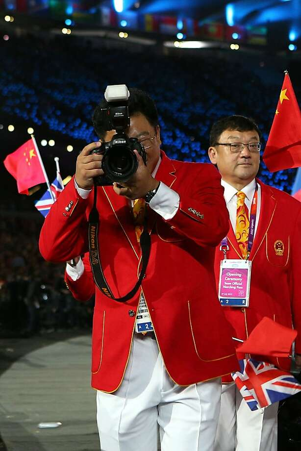LONDON, ENGLAND - JULY 27: A member of the Chinese Olympic team takes a photo during the Opening Ceremony of the London 2012 Olympic Games at the Olympic Stadium on July 27, 2012 in London, England.  (Photo by Cameron Spencer/Getty Images) Photo: Cameron Spencer, Getty Images