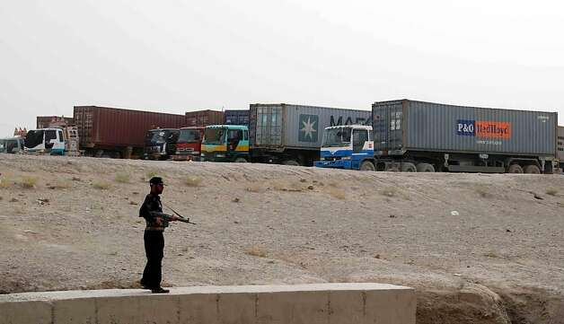 A Pakistani security serviceman stands guard beside container trucks carrying NATO supplies parked at the border town of Chaman on July 27, 2012. Pakistan has temporarily stopped NATO supply trucks crossing its northwestern border into Afghanistan over security concerns due to fears of Islamist attacks, officials said July 26. Gunmen on Tuesday attacked a convoy of NATO supply trucks, killing a driver, in the town of Jamrud near the main northwestern city of Peshawar, in the first such attack since Pakistan lifted a seven-month blockade of the border. AFP PHOTO / ASGHAR ACHAKZAIASGHAR ACHAKZAI/AFP/GettyImages Photo: Asghar Achakzai, AFP/Getty Images