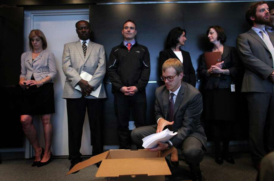 Thomas Bates with the Western Washington U.S. Attorney's office opens a box containing the agreement between the City of Seattle and U.S. Department of Justice during a joint briefing to announce an agreement on police reforms on Friday, July 27, 2012. Officials agreed to an independent monitor and court oversight of the city's police department as part of the agreement. Photo: JOSHUA TRUJILLO / SEATTLEPI.COM