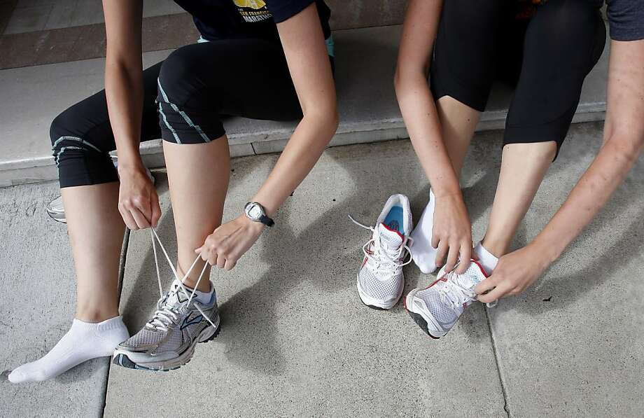 The Welch sisters prepare for a workout in front of their apartment building. Jackie and Becky Welch, sisters who live in San Francisco, Calif., will be running their first half marathon, a popular run distance,  during this years San Francisco Marathon. Photo: Brant Ward, The Chronicle