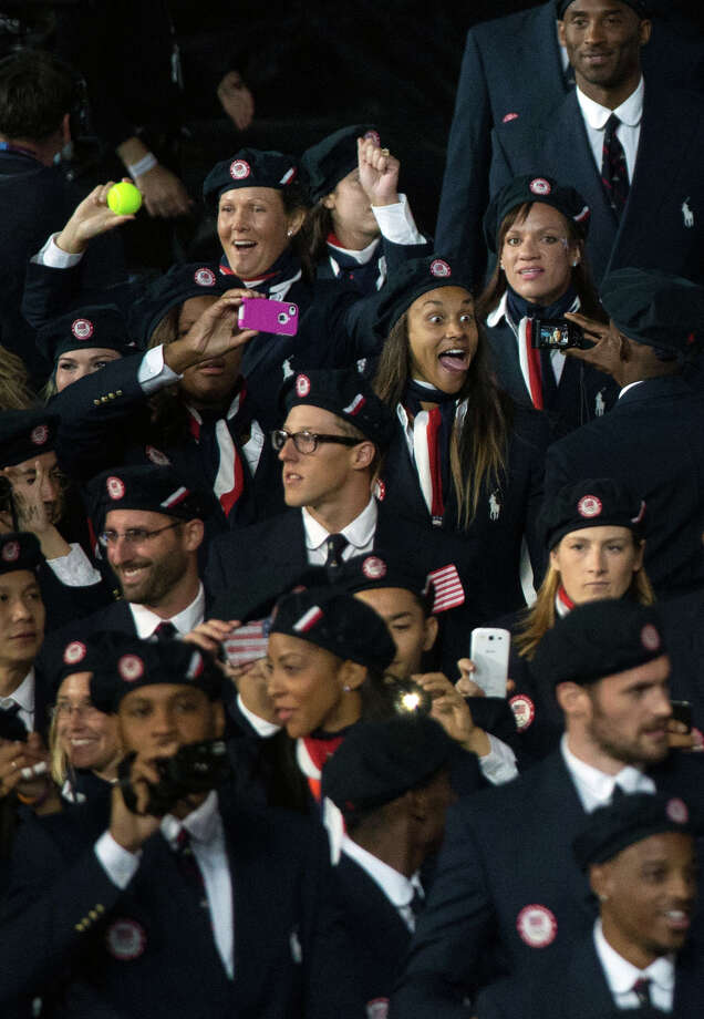 Tennis player Liezel Huber, of Houston, holds up a tennis ball as the USA enters the stadium during the opening ceremony for the 2012 London Olympics on Friday, July 27, 2012. Photo: Smiley N. Pool, Houston Chronicle / © 2012  Houston Chronicle