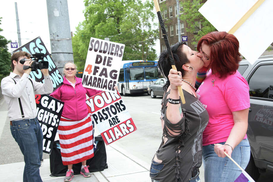 Opponents of Westboro Baptist Church Dannii Little (left) and Tiffany Peterson (right) kiss to display their support of gay rights in front of church members. Photo: Joshua Bessex / The Daily of the University of Washington