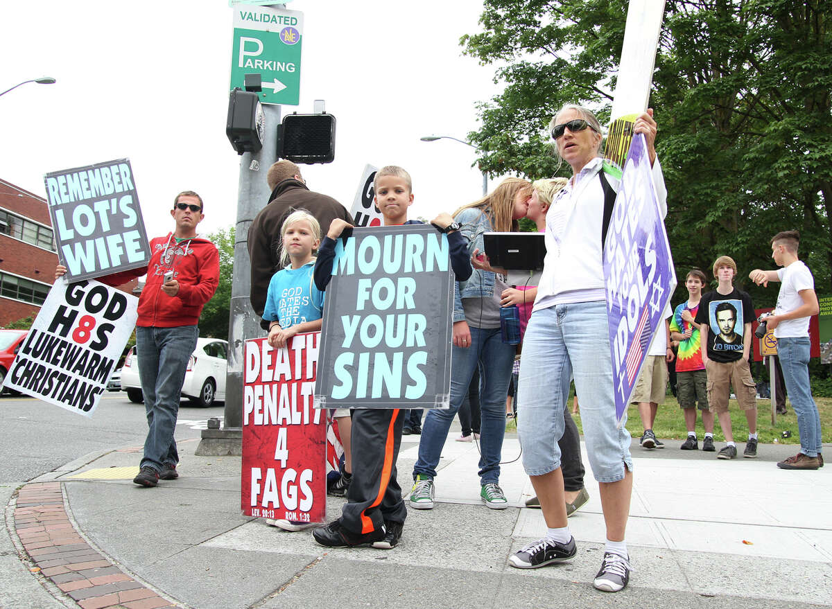 Members of Westboro Baptist Church picket on the corner of Northeast 45th Street and 15th Avenue Northeast while protesters Hayley Jones and Chelise Jacobson kiss behind them.