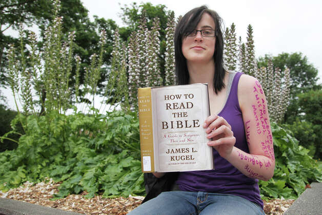 "In silent protest, Fred Demien holds up ""How To Read The Bible"" by James L. Kugel. As a youth director of a Portland church, Demien believes that Westboro sends the wrong message about God and religion"
