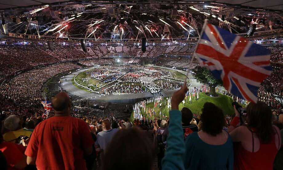 A spectator waves a flag of Great Britain as pyrotechnics light up the sky over the Olympic Stadium during the Opening Ceremony at the 2012 Summer Olympics, Friday, July 27, 2012, in London. (AP Photo/Markus Schreiber) Photo: Markus Schreiber, Associated Press