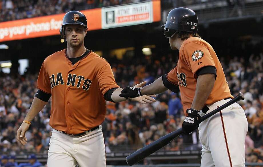 San Francisco Giants' Brandon Belt, left, is congratulated by Ryan Theriot after scoring against the Los Angeles Dodgers during the second inning of a baseball game in San Francisco, Friday, July 27, 2012. (AP Photo/Jeff Chiu) Photo: Jeff Chiu, Associated Press