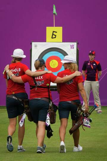 The US Archery team of Jennifer Nichols, Miranda Leek and Khatuna Lorig walk arm in arm toward the t