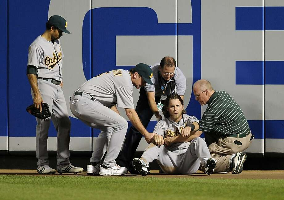 Oakland Athletics right fielder Josh Reddick, sitting, is tended to after he crashed into the wall in right field to make the last out of the baseball game on a fly ball by Baltimore Orioles' Nick Markakis, Friday, July 27, 2012, in Baltimore. With them are center fielder Coco Crisp, left, and manager Bob Melvin, second from left. The Athletics won 14-9. (AP Photo/Nick Wass) Photo: Nick Wass, Associated Press