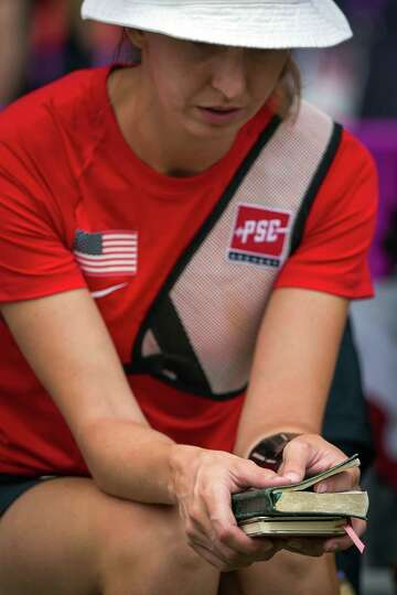 USA's Jennifer Nichols bows her head as she holds the Bible while preparing for competition to begin