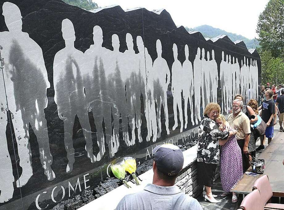 Family and friends view the 48-foot-long granite Upper Big Branch Miners monument, Friday, July 27, 2012 in Whitesville, W.Va,  On the heels of a West Virginia coal mining death, families of the 29 men killed in the Upper Big Branch mine dedicated a memorial Friday to their fallen relatives and those injured in the April 2010 explosion. (AP Photo/The Register-Herald, Rick Barbero) Photo: Rick Barbero, Associated Press