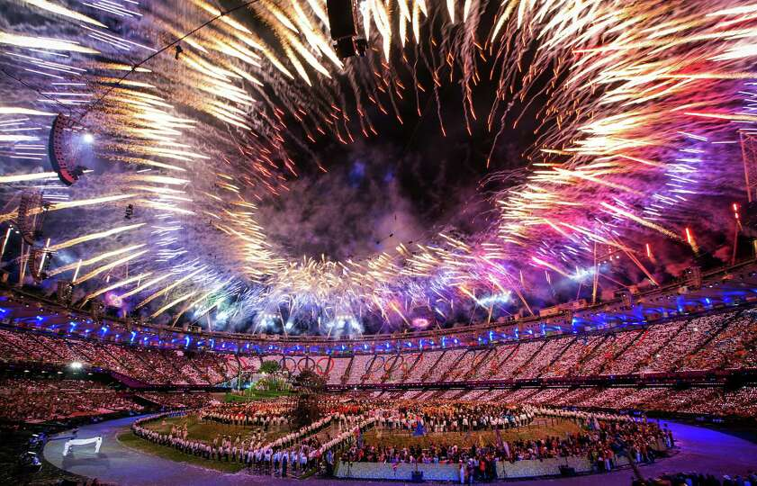 Fireworks explode as the Olympic flag, bottom left, enters the stadium during the opening ceremony f