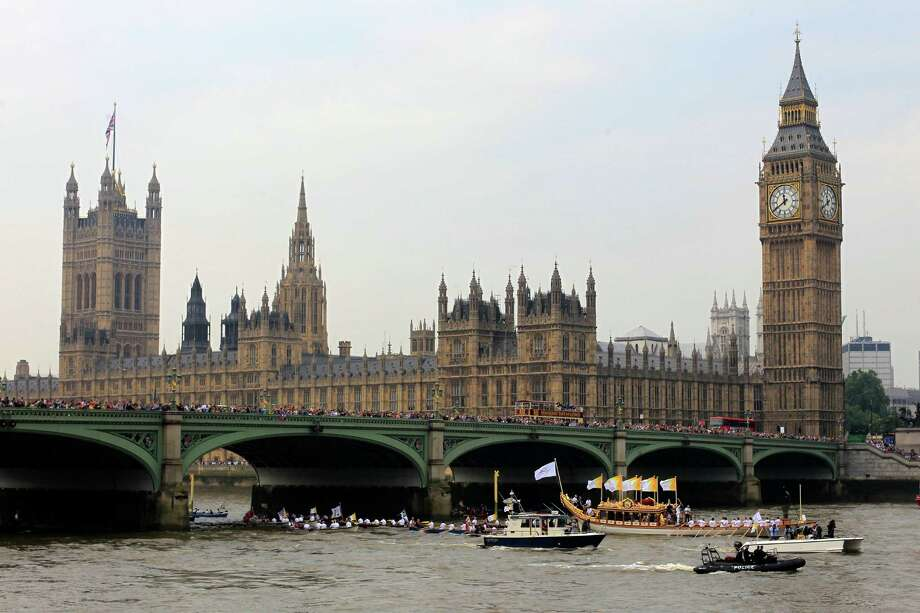 A torchbearer carries the Olympic flame on the royal barge Gloriana as it sail pass the Houses of Parliament through Westminster Bridge in London on the final day of the Torch Relayof the 2012 Summer Olympics Friday, July 27, 2012. (AP Photo/Sang Tan) Photo: Sang Tan